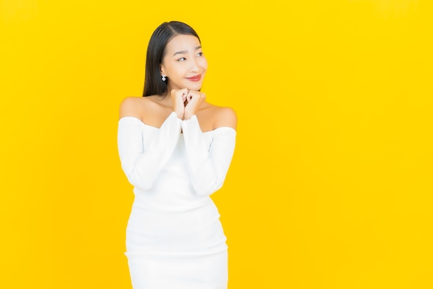 Retrato de uma bela jovem mulher asiática de negócios sorrindo com um vestido branco na parede amarela