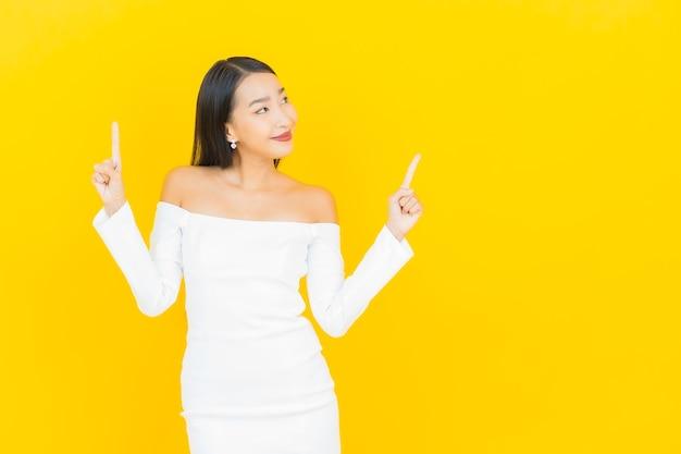 Retrato de uma bela jovem mulher asiática de negócios sorrindo e apontando para cima com um vestido branco na parede amarela