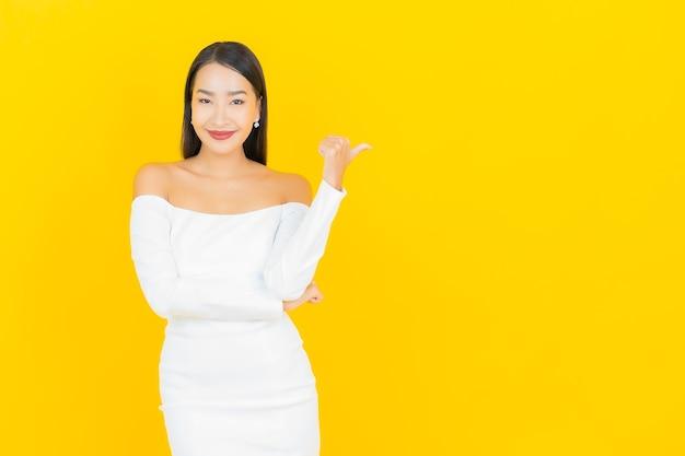 Retrato de uma bela jovem mulher asiática de negócios sorrindo e apontando para o lado com um terno branco na parede amarela