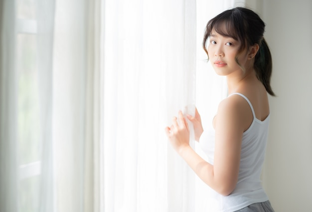 Retrato de uma bela jovem mulher asiática em pé na janela e sorrir