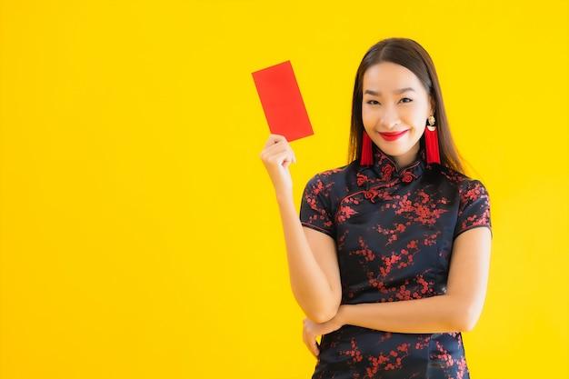 Retrato de uma bela jovem mulher asiática usa vestido chinês e mantém a letra vermelha