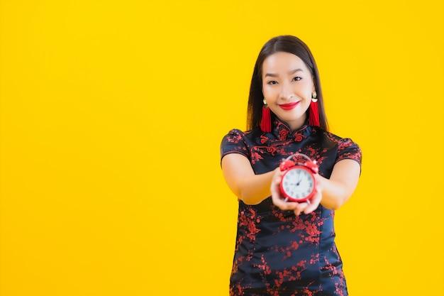 Retrato de uma bela jovem mulher asiática usa vestido chinês e mostra o relógio