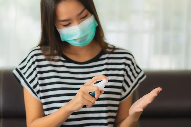 Retrato de uma bela jovem mulher asiática usando álcool spray para limpar a mão