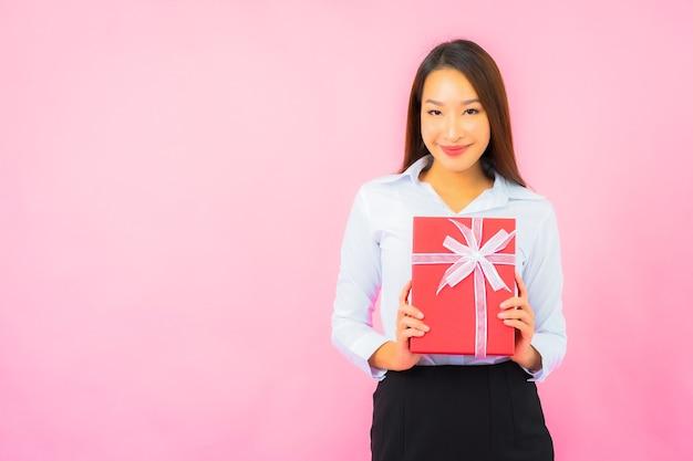Retrato de uma bela jovem mulher de negócios asiática com caixa de presente vermelha na parede cor de rosa