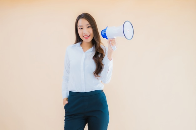 Retrato de uma bela jovem mulher de negócios asiática com megafone para comunicação
