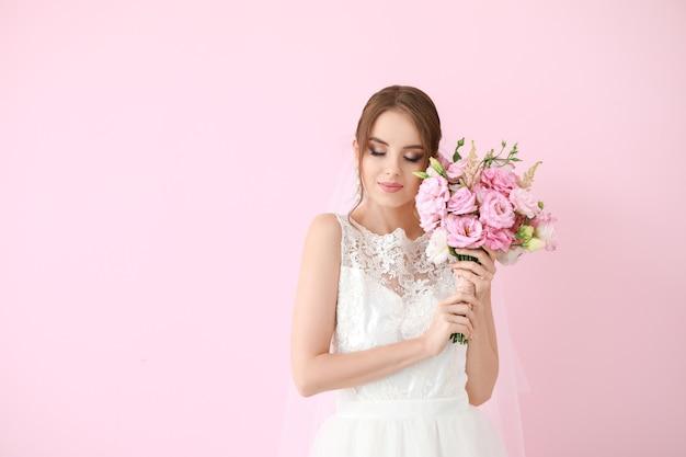 Retrato de uma bela jovem noiva com buquê em cores