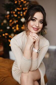 Retrato de uma bela jovem perto da árvore de natal