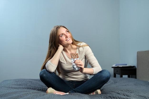 Retrato de uma bela jovem positiva com chocolate com avelãs, mulher feliz sentada em casa na cama, espaço de parede cinza