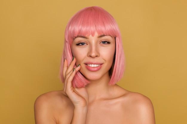 Retrato de uma bela jovem positiva com penteado bob rosa, olhando com o rosto calmo e levando a mão à bochecha, posando sobre parede de mostarda