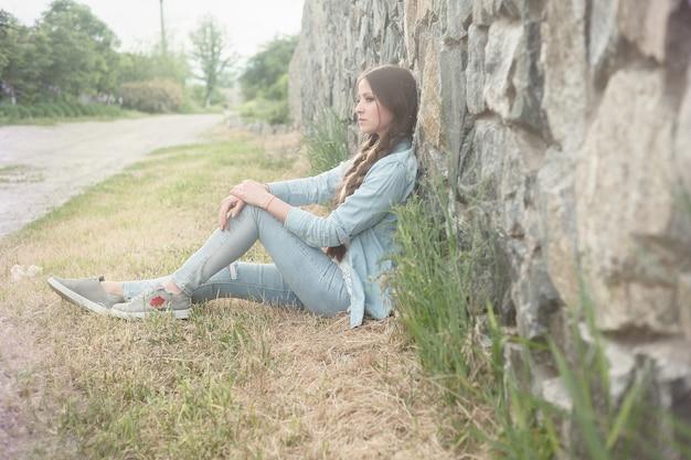 Retrato de uma bela jovem romântica na zona rural ao pôr do sol. garota atraente em roupas jeans Foto Premium