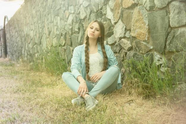 Retrato de uma bela jovem romântica na zona rural ao pôr do sol. garota atraente em roupas jeans
