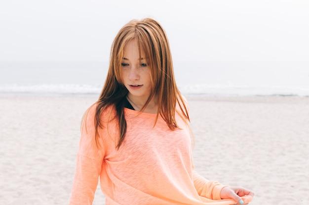 Retrato de uma bela jovem ruiva na praia