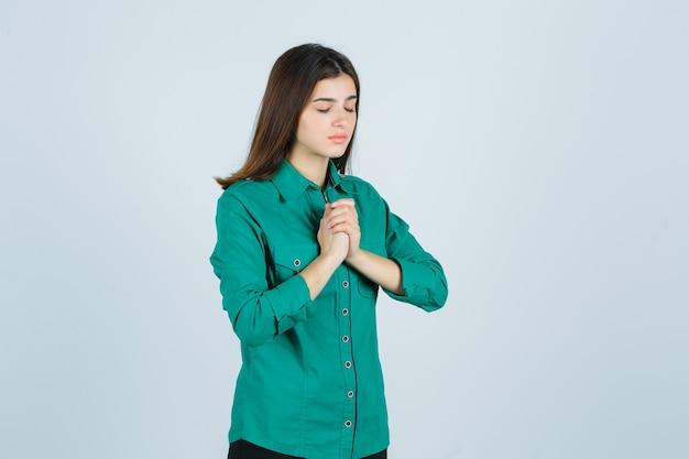 Retrato de uma bela jovem segurando as mãos em gesto de oração em uma camisa verde e olhando esperançoso de frente