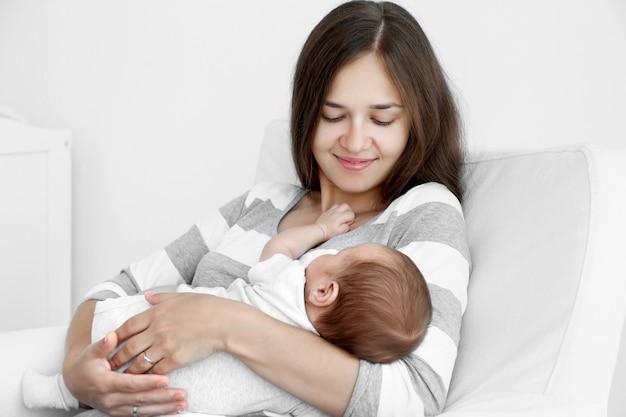 Retrato de uma bela jovem segurando um bebê dormindo em casa