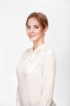 Retrato de uma bela jovem sensual loira em camisa branca sorrindo e olhando para a câmera