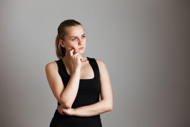 Retrato de uma bela jovem sonhadora pensando. tocar na cara. sobre a parede cinza. copie o espaço.