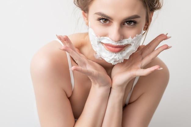 Retrato de uma bela jovem sorridente caucasiana com espuma de barbear em poses de rosto em fundo branco.