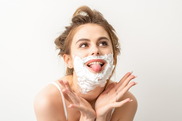 Retrato de uma bela jovem sorridente caucasiana, posando com espuma de barbear no rosto, mostrou a língua no fundo branco.