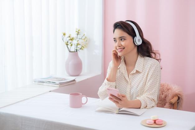 Retrato de uma bela jovem sorridente feliz sentada no escritório, ouvindo música por fones de ouvido