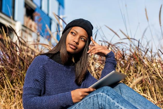 Retrato de uma bela jovem sorridente mulher africana usando o tablet pc computador sentado na cidade em um dia ensolarado