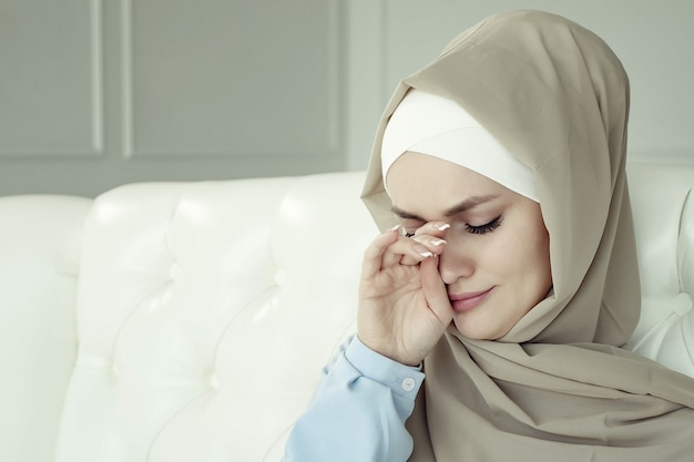 Retrato de uma bela jovem triste chorando mulher muçulmana no hijab bege está sentado no sofá em casa. ela chora e enxuga as lágrimas com as mãos, tonificada