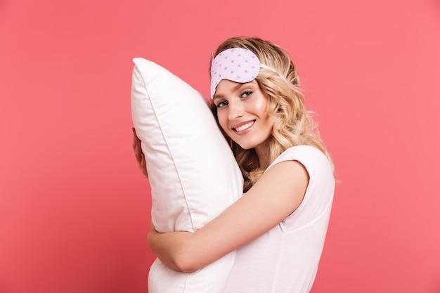 Retrato de uma bela jovem usando máscara para dormir, segurando e deitada em um travesseiro branco isolado na parede vermelha