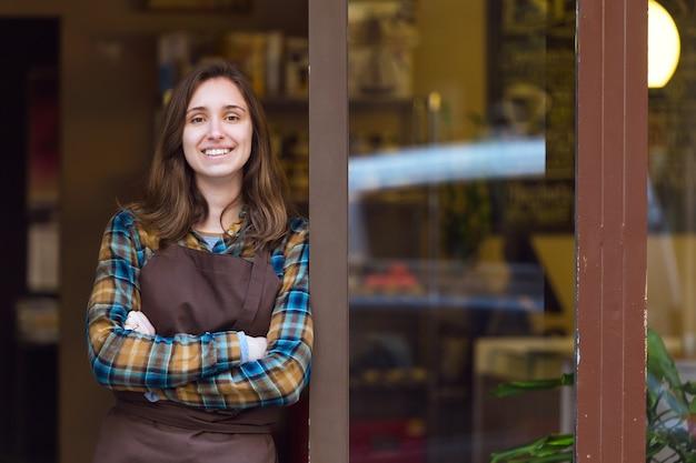 Retrato de uma bela jovem vendedora olhando para a câmera e encostado no batente da porta de uma loja orgânica.