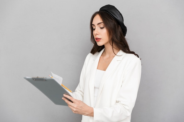 Retrato de uma bela jovem vestida com uma jaqueta em pé sobre um fundo cinza, segurando o tablet