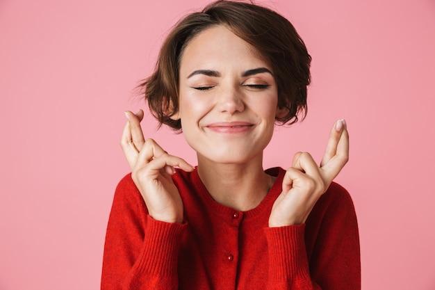 Retrato de uma bela jovem vestindo roupas vermelhas em pé isolado sobre um fundo rosa, segurando os dedos cruzados para dar sorte