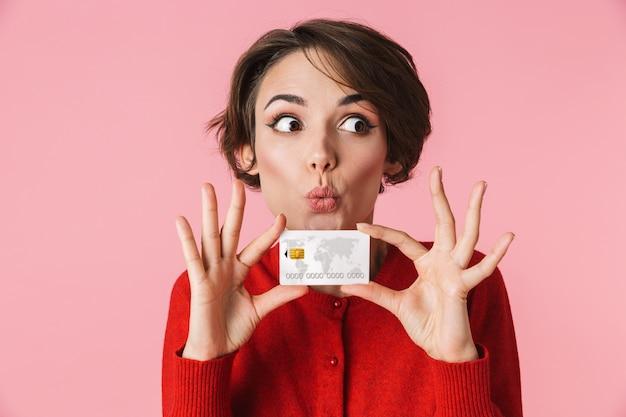 Retrato de uma bela jovem vestindo roupas vermelhas em pé isolado sobre um fundo rosa, segurando um cartão de crédito