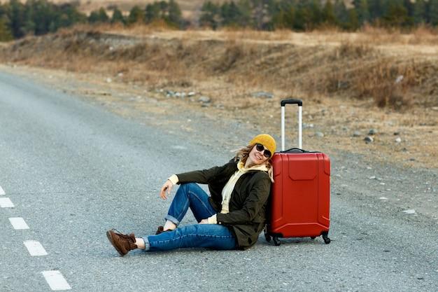 Retrato de uma bela jovem viajante sentada no meio de uma estrada nas montanhas ao lado de uma mala vermelha