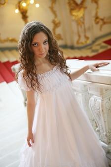 Retrato de uma bela jovem vitoriana em vestido branco. palácio da rússia.