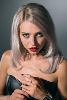Retrato de uma bela loira com lábios vermelhos em um fundo escuro em uma gola com pontas