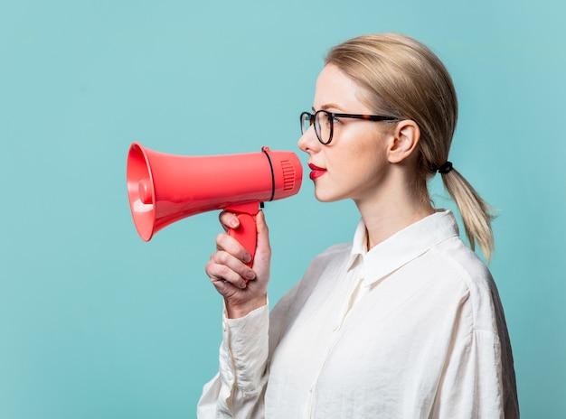 Retrato de uma bela loira em uma camisa branca com alto-falante na parede azul