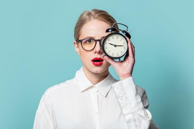 Retrato de uma bela loira em uma camisa branca com despertador na parede azul