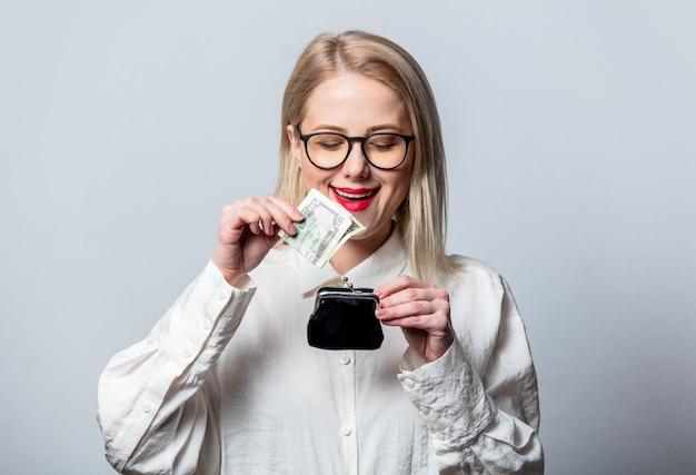 Retrato de uma bela loira em uma camisa branca com dinheiro e carteira na parede branca