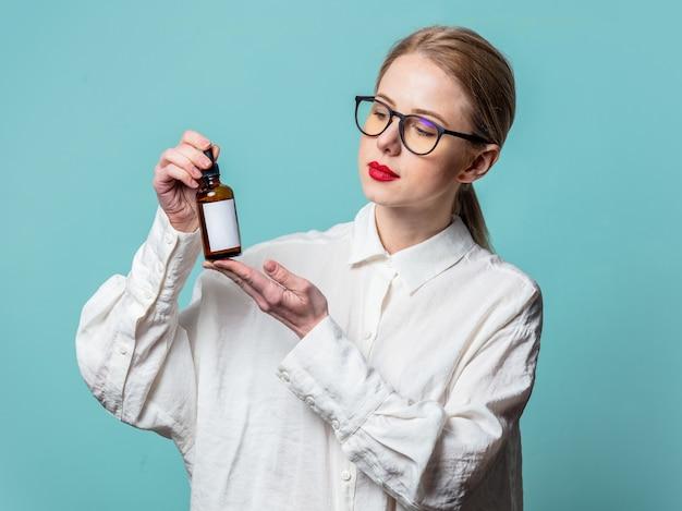 Retrato de uma bela loira em uma camisa branca com frasco cosmético na parede azul