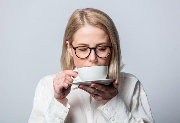 Retrato de uma bela loira em uma camisa branca com uma xícara de café na parede branca