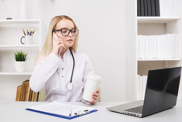 Retrato de uma bela médica sorridente enquanto fala no smartphone e preenche um boletim médico