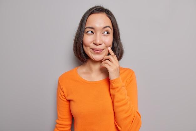 Retrato de uma bela modelo asiática relembrando seu primeiro encontro com o marido, com uma expressão de alegria sonhadora, sorrisos suavemente concentrados e vestindo um macacão laranja casual em poses internas contra uma parede cinza
