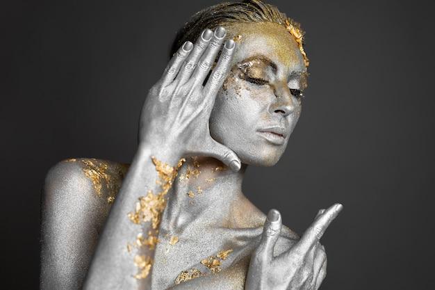 Retrato de uma bela modelo feminino com tinta dourada e prata na pele e no cabelo no estúdio.