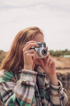 Retrato de uma bela modelo tirando uma foto com uma câmera analógica