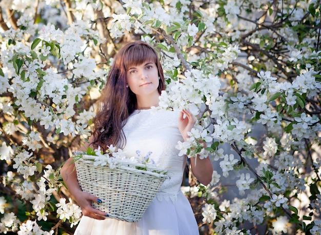 Retrato de uma bela morena com cesta branca no parque de macieiras de flor. conceito de harmonia, paz e tranquilidade.