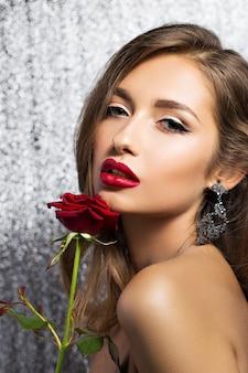 Retrato de uma bela morena com uma rosa vermelha
