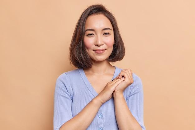 Retrato de uma bela morena jovem asiática tem expressão satisfeita pele saudável beleza natural mantém as mãos juntas parece misteriosamente na frente vestida com jumper azul poses dentro de casa sozinho