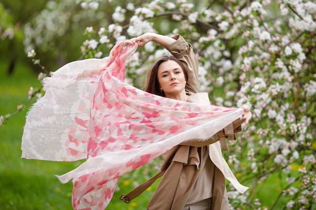 Retrato de uma bela morena jovem no jardim de macieira flor na primavera. aproveite a natureza. menina saudável ao ar livre. conceito de primavera. linda garota no pomar