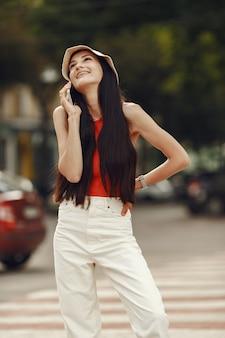 Retrato de uma bela morena. modelo na cidade de verão. mulher caminha com o telefone celular.
