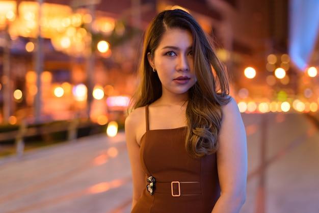 Retrato de uma bela mulher asiática ao ar livre em bangkok, tailândia, à noite