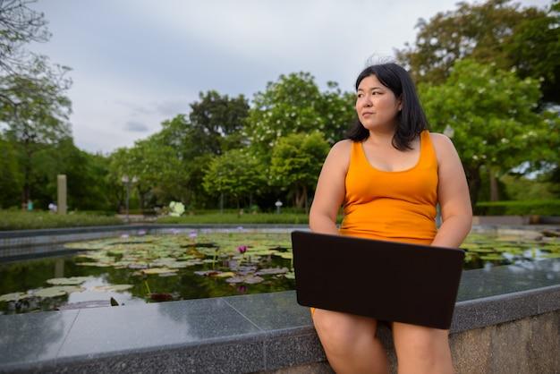 Retrato de uma bela mulher asiática com excesso de peso relaxando no parque na cidade de bangkok, tailândia
