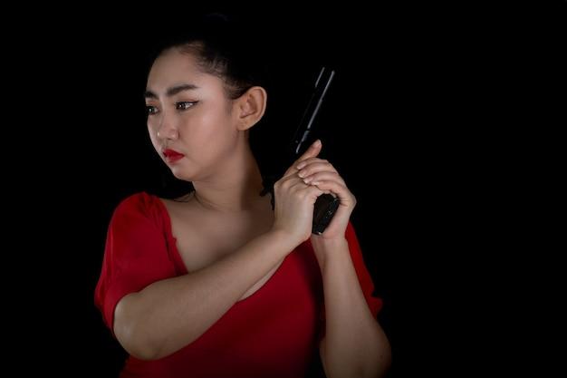 Retrato de uma bela mulher asiática usando um vestido vermelho com uma das mãos segurando uma pistola 11 mm a